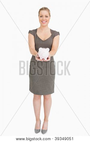 Woman holding a piggy bank against white background