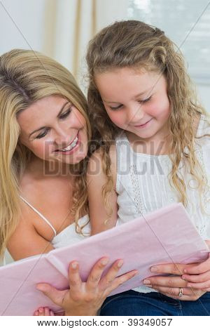 Smiling daughter and mother reading storybook together