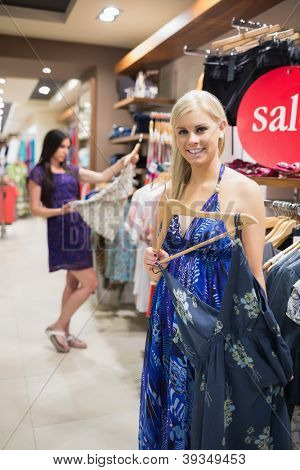 Smiling woman standing beside clothes rail in shopping mall
