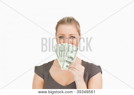 Woman hiding her mouse with dollars banknotes against white background