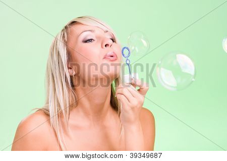 Attractive Young Woman Blowing Bubbles