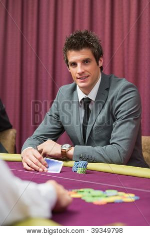 Man sitting at the table smiling while holding cards at a casino