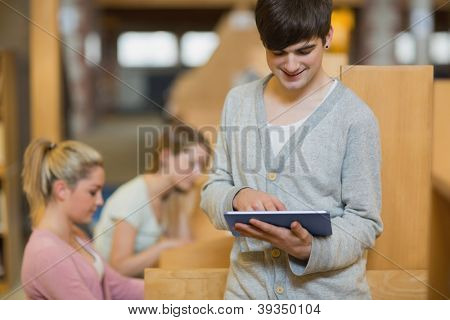 Man standing in college library holding a tablet computer while smiling