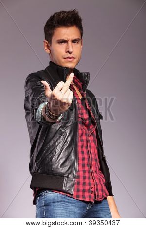 young man in leather jacket and jeans giving you the middle finger