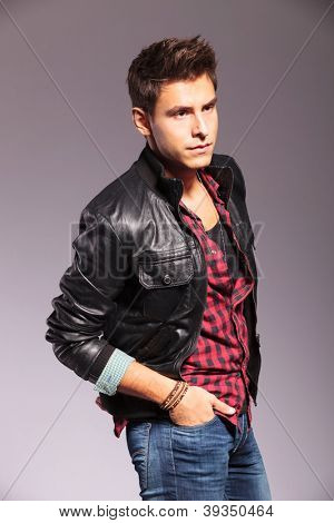 side view of a casual man in leather jacket looking away from the camera and standing with hands in pockets