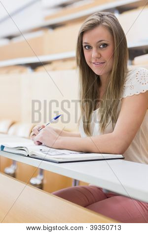 Girl sitting at the lecture hall writing notes and smiling