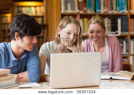 Students sitting at a library with laptop smiling