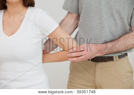 Close-up of a doctor examining the arm of a patient in a room