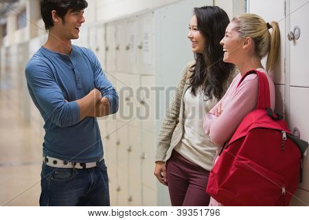 Friends talking in college hallway beside lockers