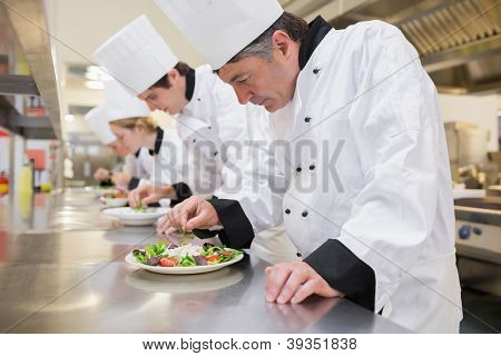 Chef's preparing their salads in the kitchen