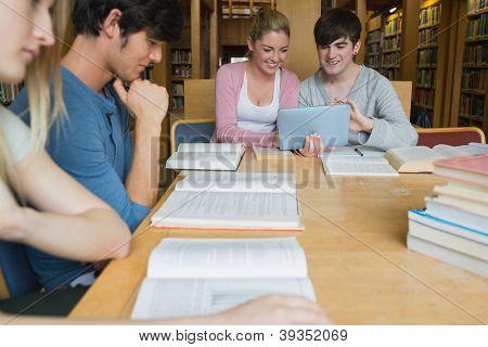 Alunos na biblioteca estudando com dois usando o tablet pc na faculdade