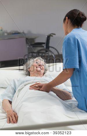 Nurse taking care of an elderly patient in hospital ward