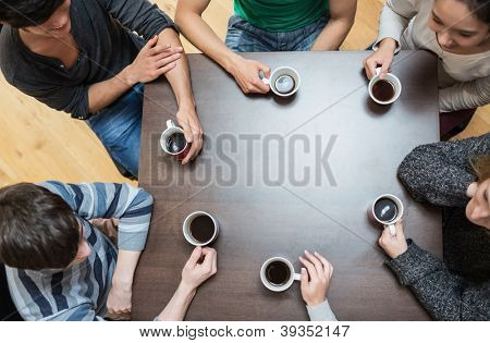 Students sitting around table drinking coffee in college cafe