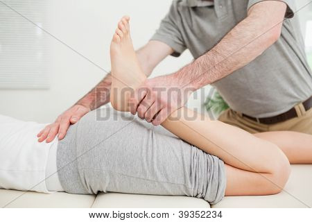 Close-up of a woman lying while being stretched in a room