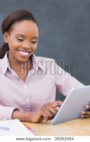 Teacher smiling while using a tablet computer in a classroom