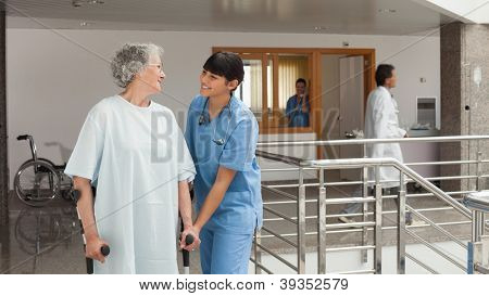 Doctor's assistant helping an old woman walking with crutches in a hospital