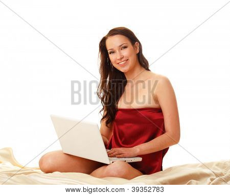 Young woman  with laptop sitting on bed isolated on white background