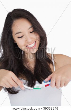 Woman smiling while holding a toothbrush and toothpaste against white background