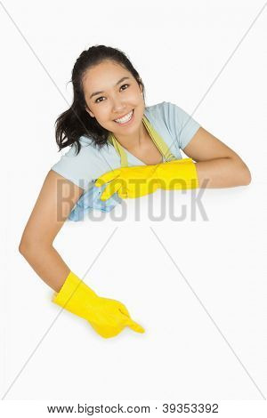 Happy cleaning lady in rubber gloves and apron pointing to white surface