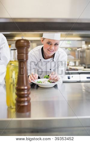 Smiling chef garnishing a salad and looking up in kitchen