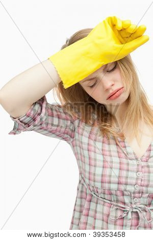 Tired woman wearing cleaning cloves against white background