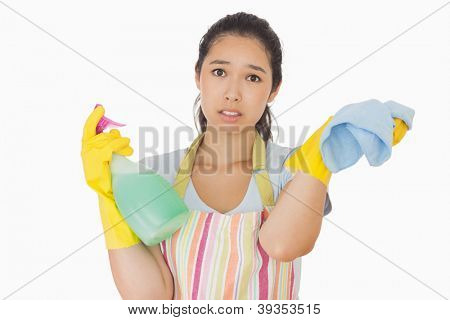 Weary woman wearing apron and gloves with spray bottle and rag