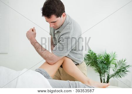 Brown-haired physiotherapist massaging the leg of a woman in a room