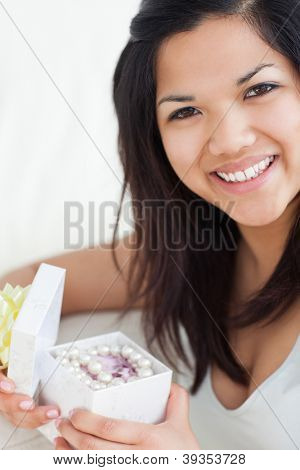 Close-up of a smiling woman holding an open gift box in a living room