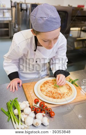 Chef finishing off a pizza in kitchen