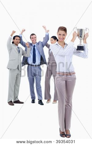 Woman holding a cup with people dressed in suits acclaiming in background