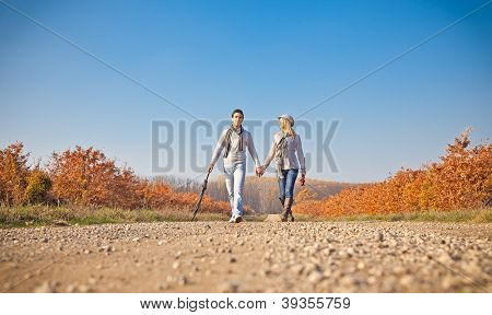 Romantic young beautiful couple with umbrella on autumn walk
