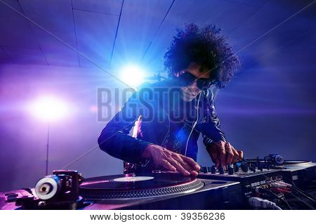nightclub dj playing music on deck with vinyl record headphones light flare clubbing party scene