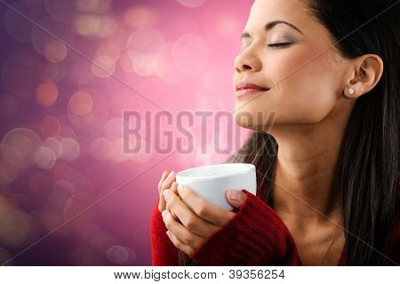 woman enjoying hot steaming cup of coffee with bokeh lights and beautiful portrait