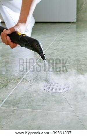 Mujer de limpieza del desagüe en el baño con vapor