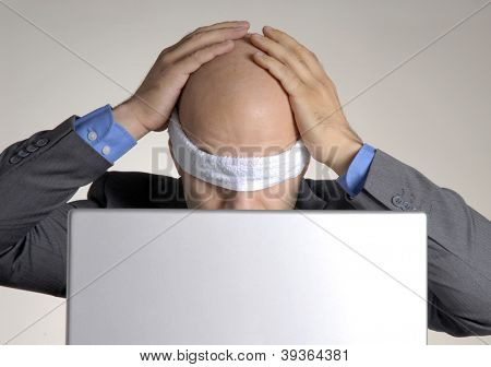 Stressed blindfolded bald man working on computer.