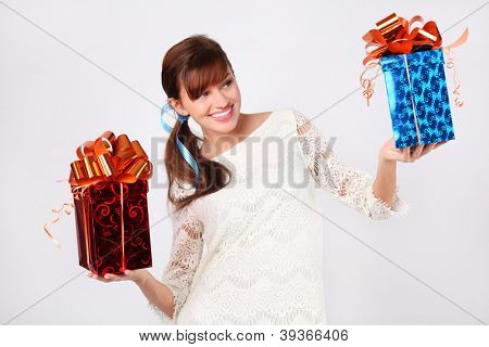 Pretty woman in white dress compares red and blue boxes with gifts.