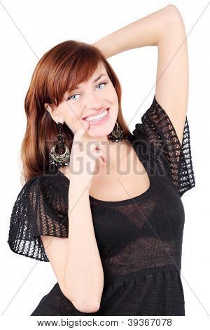 Happy girl in black dress and bid earrings smiles and touches her chin isolated on white background.