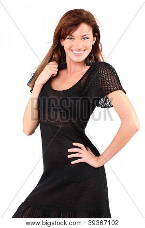 Beautiful girl in black dress and bid earrings smiles and holds her hair isolated on white background.