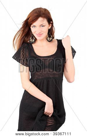 Sexy girl in black dress and bid earrings smiles and holds her dress isolated on white background.
