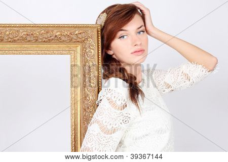Beautiful melancholic woman in white dress stands near big gilt frame.