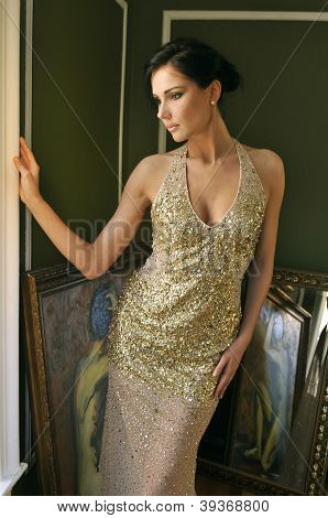 Pretty woman in vintage gown posing in room