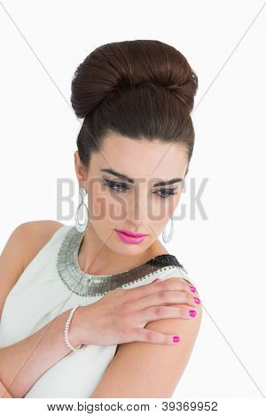 Woman touching her shoulder while dressed in mod style on white background