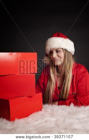 Pretty Young Woman In Santa Hat Looking At Three Gifts