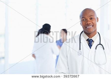 Doctor standing in a well-lit room with his team in the background