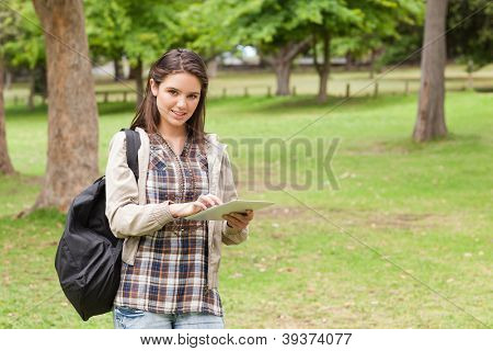 Young student using a tactile tablet in a park