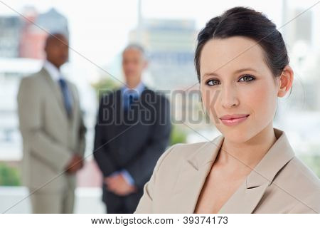 Young smiling secretary standing in front of two businessmen in a relaxed way