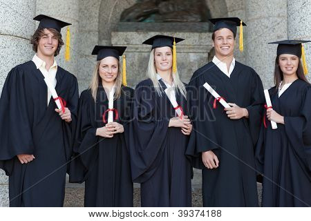 Smiling graduates posing in front of the university