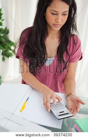 Brunette student taking a calculator to do her homework