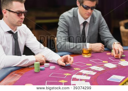 Men sitting at the table wearing sun glasses placing bet