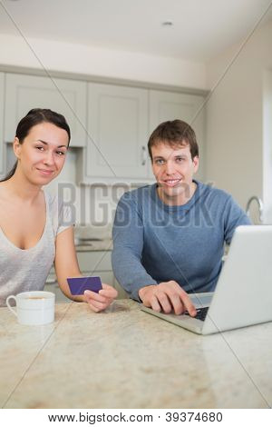 Couple sitting in the kitchen with a laptop and a credit card while drinking coffee